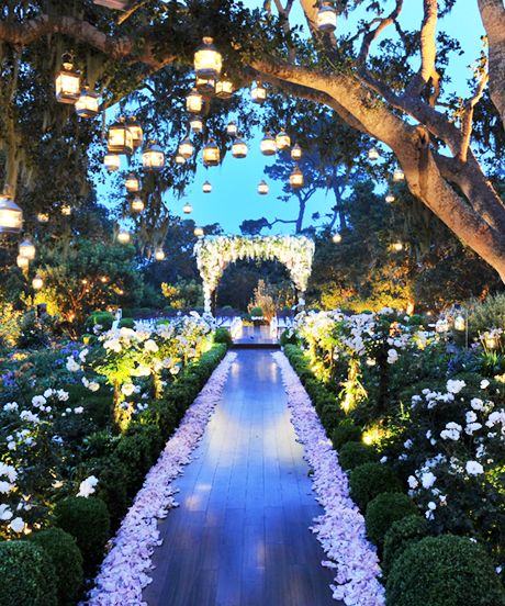 "An Enchanted Garden ""Create an Enchanted Garden where no one exists. To improve on nature, we rented hundreds of plants and added fresh-cut flowers in full bloom. Placing small lanterns in the existing trees and throughout the garden added just the right amount of magic to the setting. Finally, we placed a simple wooden aisle leading to the main focal point of the ceremony: a lavish flower-encrusted gazebo."""