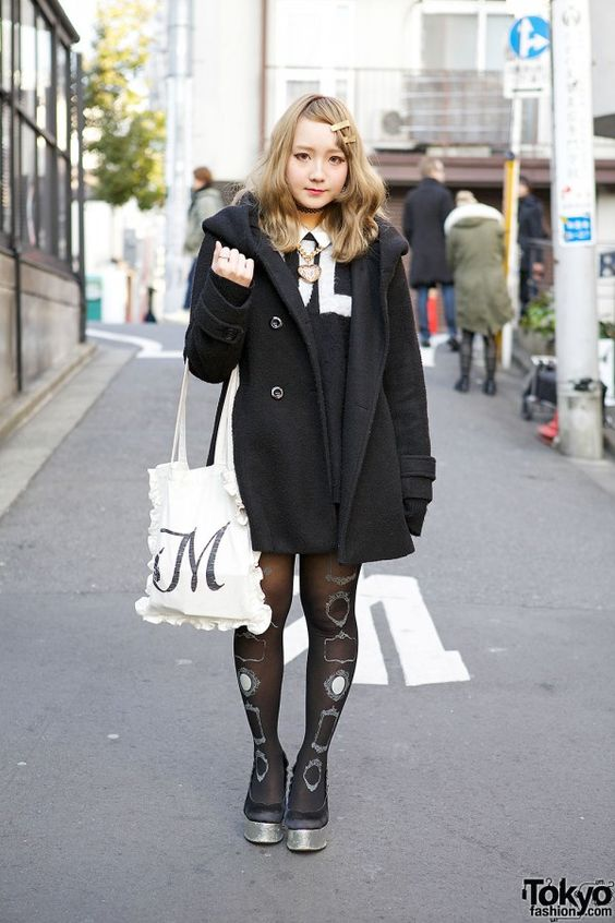 Marikofu is 20-year-old student whose monochrome look caught our eye in Harajuku. Her black coat is from Nice Claup, worn over an Jouetie sweater and white shirt. Her ruffled tote is a resale piece, and her star wedge shoes are from Jouetie. Her gold hairpins are also resale purchases, her heart necklace is handmade, and her ring is Vivienne Westwood. We also noticed a tattoo necklace and her frame print tights. (Yokyo Fashion, 2014)