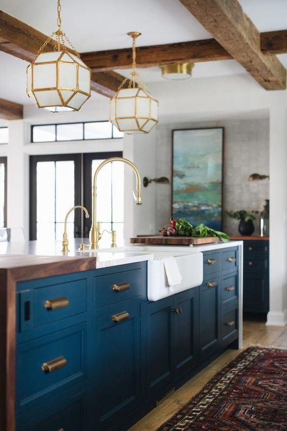 I love the blue cabinets; the nook at the end seems multi-functional. The pendants are awesome - and I love all the brass accents
