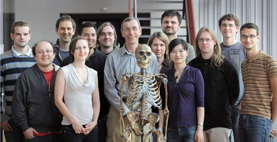 """Members of """"The Neandertal Genome Project"""" at the Max Planck Institute for Evolutionary Anthropology pose with a Neanderthal skeleton. The initial draft of the genome was published in """"Science"""" on May 7, 2010 and  """"results indicate that Neandertals are slightly more closely related to modern humans outside Africa. The team also identified several genomic regions that appear to have played an important role during human evolution."""""""