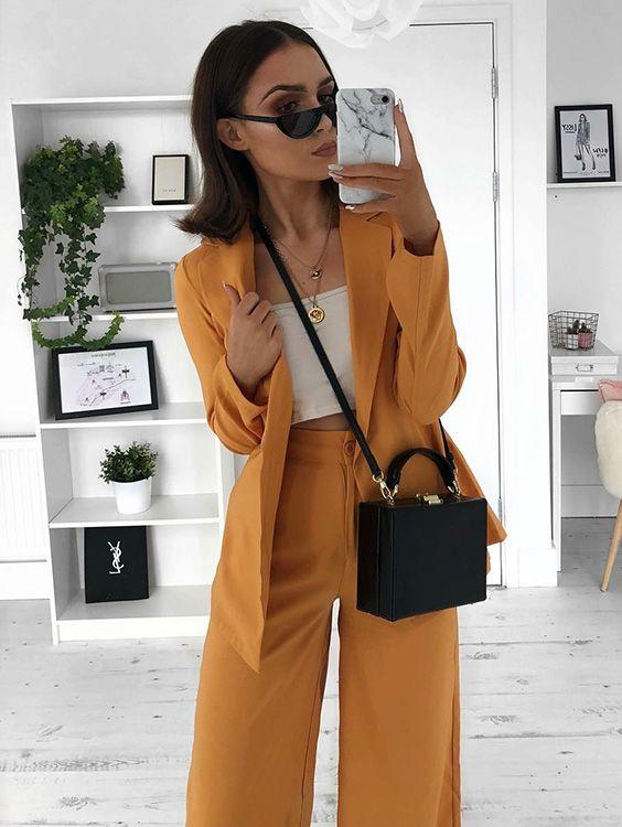Selfie perfeita: 10 capinhas de celular trendy que dão um up nas fotos de espelho. Terninho, blazer amarelo, calça de alfaiataria amarela, top cropped branco, bolsa quadrada, mini óculos, capinha de mármore carrara