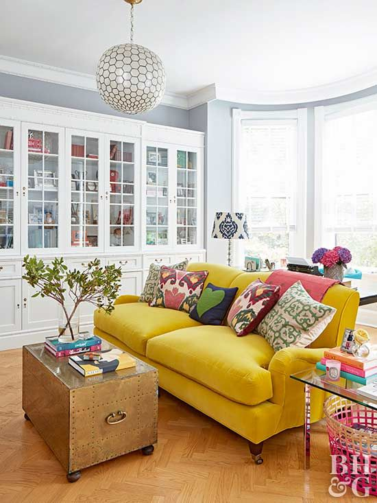 Although they might seem like an afterthought, throw pillows are an easy solution for trying out trends in pattern and color without the major commitment. #livingroom #livingroomdecor #lowcostmakeover #livingroommakeover #bhg