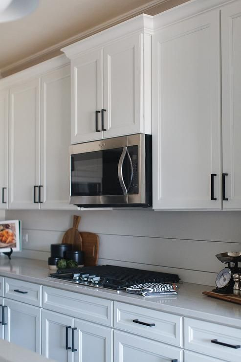 White Shaker Kitchen Cabinets Accented With Oil Rubbed Bronze Pulls And An Off White White Shaker Kitchen Cabinets White Shaker Kitchen Shaker Kitchen Cabinets