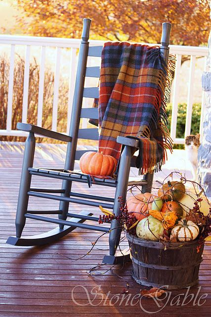 Plaid wool throw in fall colors  over the porch rocker. Love the display of gourds in the bushel basket!