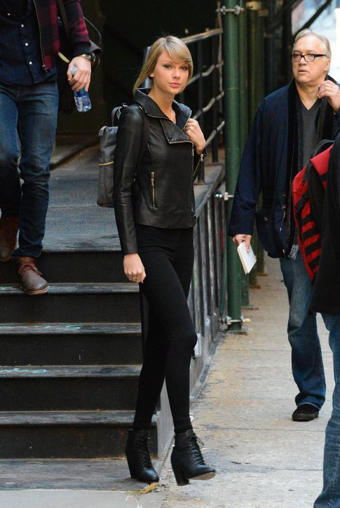 Taylor Swift in a black moto jacket, black pants, and mini backpack