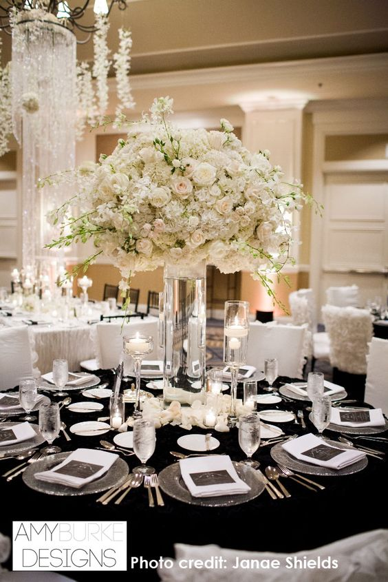 Tall clear glass vase with large white round arrangement with Dendrobium Orchids peeking out. @janaeshields #reception Location Ritz Carlton Half Moon Bay