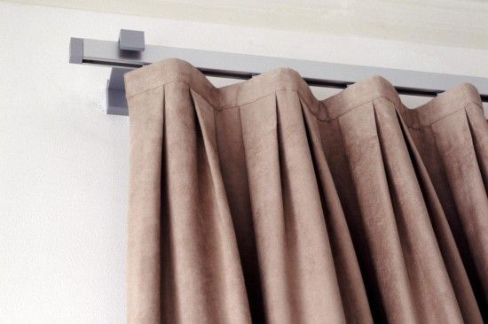 Inverted box pleat top banded drapery on decorative traverse rod.