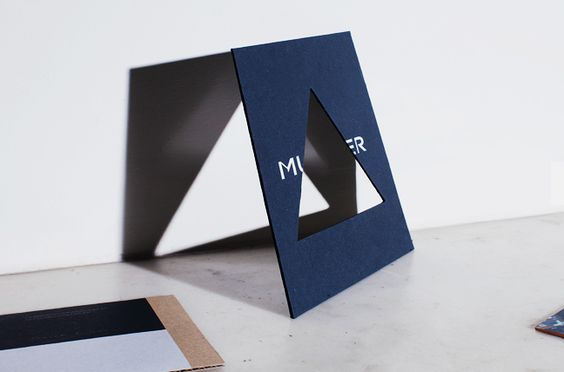 Mugler: A midnight-blue card with a graphic cut-out introduces Mugler on the front, and his show details on the back