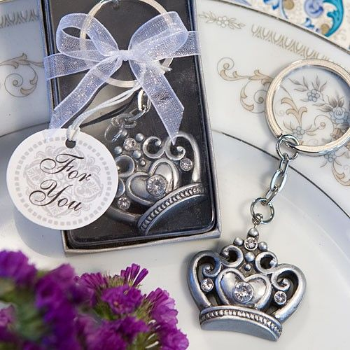 """Give your  guests something special to hold the keys to their """"castle"""" with these Royal  Favor Collection crown design key ring favors    Everyone likes to be treated  like royalty sometimes.  So why not help your family and friends feel like  kings and queens each time they reach for their keys with these fun and  functional keepsakes?  From Fashioncraft's Royal Favor Collection,  each measures 1.5"""" x 3""""and has a durable pewter finish poly resin crown charm,  with cutout ornamental detail…"""