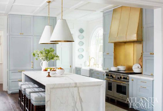 Light blue kitchen with waterfall marble island and brass range hood - on Hello Lovely Studio