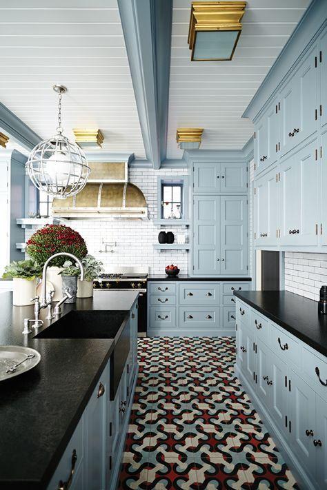 light blue kitchen cabinets, black countertop, tile floor, brass flush fixtures + range