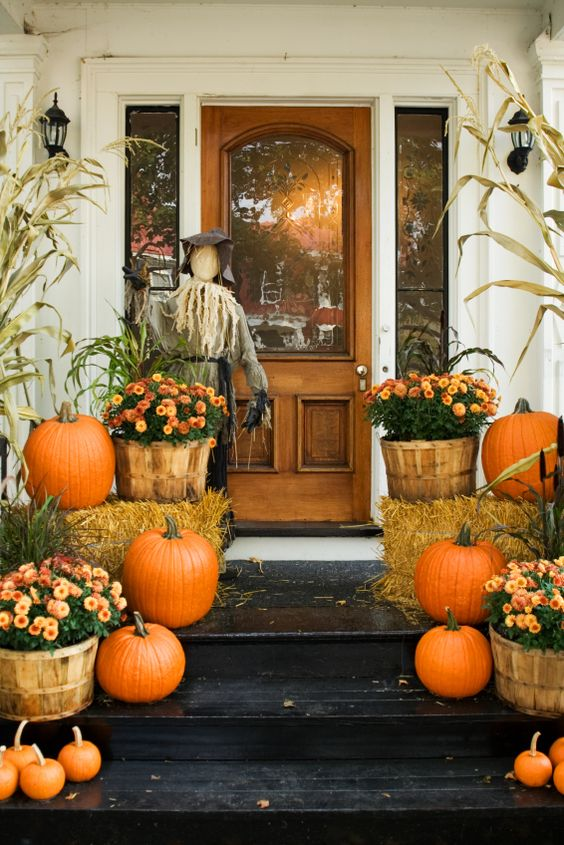 Charming autumn decorations greet visitors to this front door. A scarecrow, pumpkins, hay bales and flowers celebrate the arrival of fall!