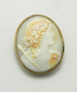 A beautiful antique cameo brooch. This features a classical lady with a laurel wreath in her hair. She has a mans head brooch pinned to her right shoulder and is carrying a scepter. Anyone know who this classical figure represents? The cameo has been carved from shell and is set as a brooch .The brooch frame is gold plated. This cameo brooch will be from the Victorian ear, it measures about 5 cms high .  There is an attached safety chain