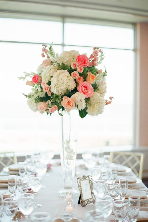 We LOVE how this tall centerpiece stands out around a neutral, white table! #flowers #weddingdecor