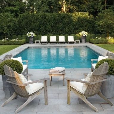 Grass, grey stone paving, gorgeous pool furniture and I love the potted flowers. Lots of green