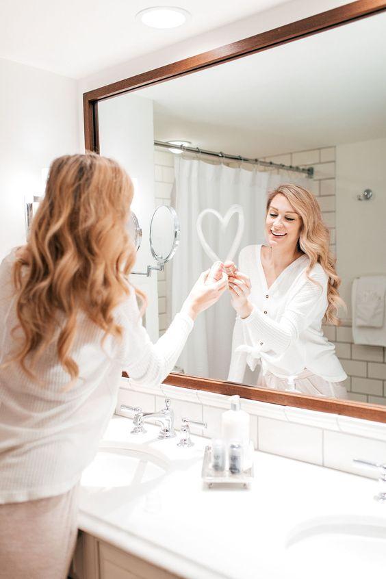 mujer frente al espejo dibujando un corazón