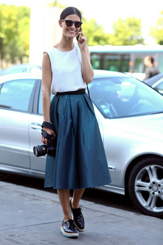 Flared skirt with a print, sleaveless white vest tucked in, and I'd probably choose Toms instead of those shoes. Simple, yet beautiful.