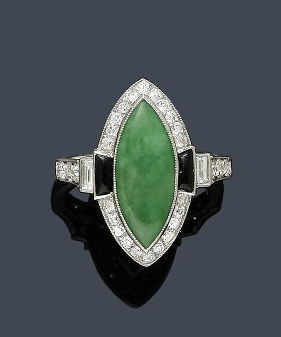 Jade ring with 1 navette-shaped jade within a border of diamonds, flanked by 2 trapeze-cut onyxes and 2 baguette-cut diamonds, circa 1930