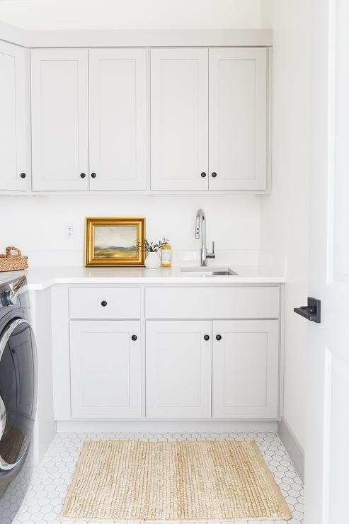 A Jute Rug Sits On White Hexagon Laundry Tiles In Front Of Light Gray Shaker Laundry Room Cabinets Contrasted Wit Laundry Room Cabinets Grey Laundry Rooms Home