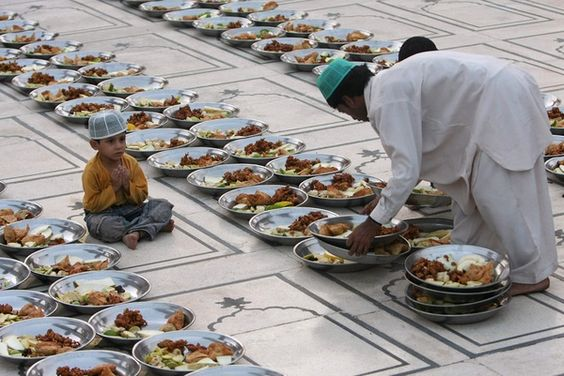 A Pakistani Muslim arranges food stuff for Iftar, a time to break the fast, on the first day of Ramadan, as a child looks on at a mosque in Karachi, Pakistan on Sunday, Aug. 23, 2009. (AP Photo/Fareed Khan) # ramadan