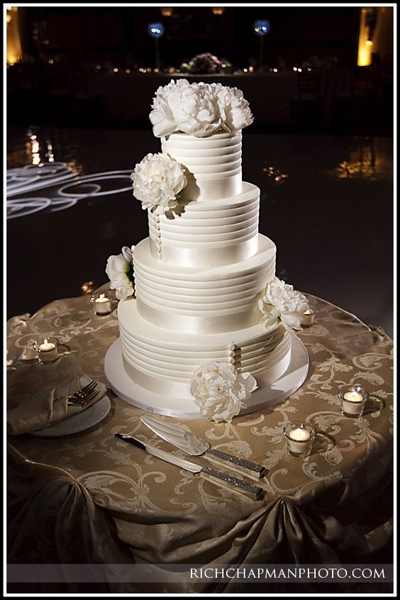 The classic white, the gorgeous flowers, the clean lines, and the little dots that look like the buttons on the back of a wedding gown.   I love this so much, I'm calling dibs on this right now. From Take the Cake bakery!
