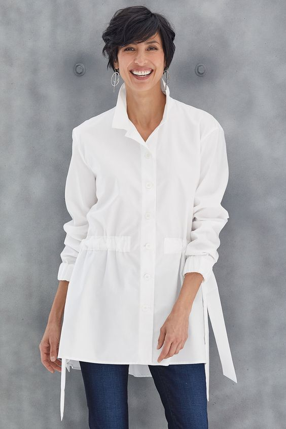Lennox Cinched Shirt by Mona Thalheimer . In impeccably tailored poplin, the classic big shirt becomes something entirely extraordinary with updates like a subtle high-low hem and shape-enhancing ties at the waist.