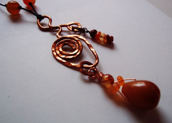 """Raw Copper Spiral Carnelian Healing Crystal Pendant Necklace   Hand hammered and wired raw copper pendant with small faceted Carnelians and large teardrop Carnelian, waxed linen cord with four round Carnelian beads   Measures, cord 27"""" with slip knot fastener, pendant 3.1/2 """"  Carnelian  Like the unexpected fire of a sunset, or the first flash of autumn brilliance, Carnelian captivates. Its bold energy brings a rush of warmth and joy that lingers, stimulating and empowering. Known as a…"""