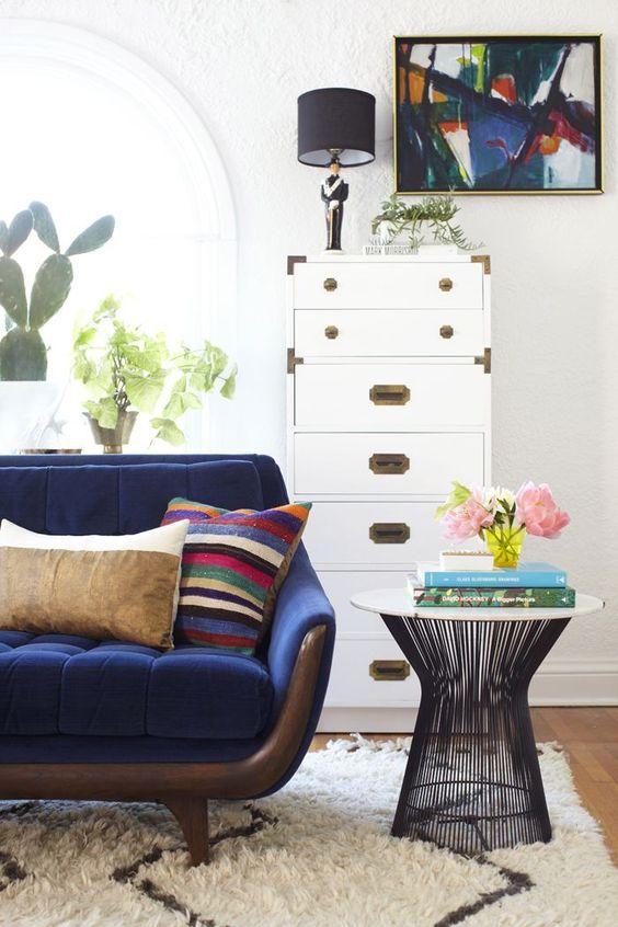 Mesa lateral aramada em formato trapezoidal e sofá pés palito.