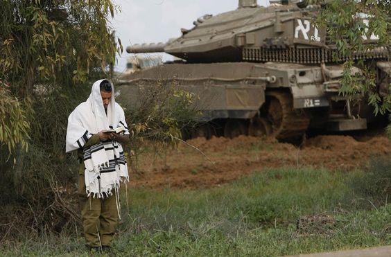 IDF soldier praying by tank.