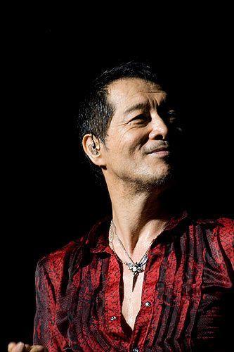 赤と黒のシャツを着て微笑んでいる矢沢永吉の画像