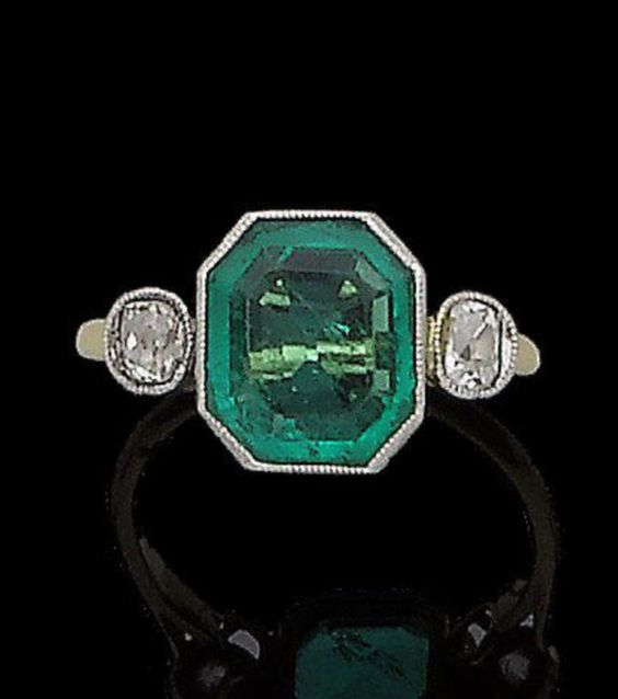 An art deco emerald and diamond ring, circa 1925 Of bi-coloured design, the cut-cornered step-cut emerald between two cushion-shaped diamonds, in millegrain collet-settings, split to gallery, later shank