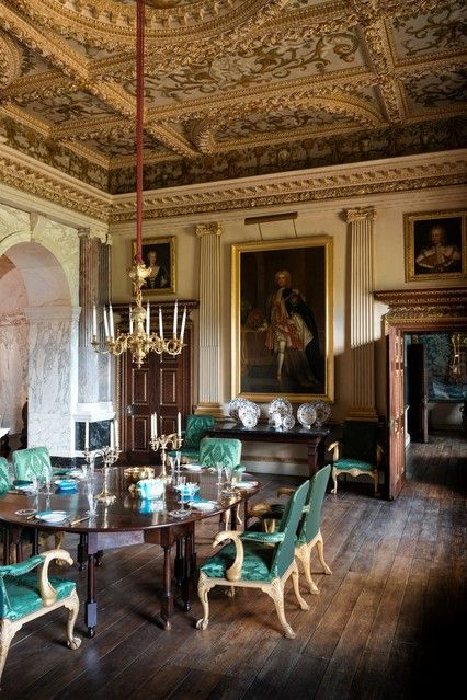 "Sir Robert Walpole entertained in Houghton Hall's ""marble parlor"" dining room. Paintings of George I and Queen Caroline flank the central portrait of Walpole.:"