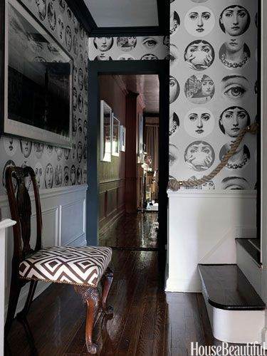 In the hallway of his Manhattan apartment, designer Eric Cohler added graphic moldings in Farrow & Ball Off-Black, Fornasetti wallpaper from Cole & Son: