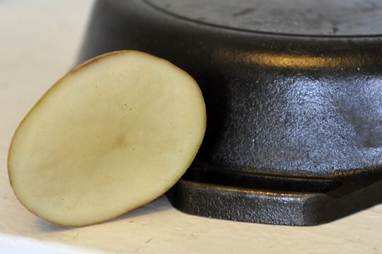 Clean iron skillet rust with sliced raw potato