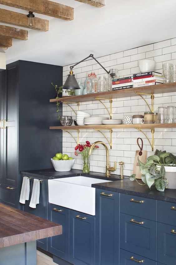 These blue cupboards help give a little bit of color and accent to the soapstone counters on top of them. It's a whole lot of dark, but with the white backing it definitely looks fun and vibrant instead of dark and depressing.