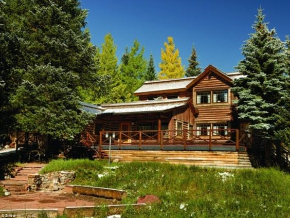 The magnificent exterior of the American Lakes Cabin, which is shrouded by trees...