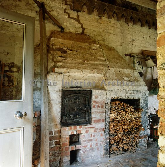 A pile of firewood is stored next to an old wood-burning stove in the utility room