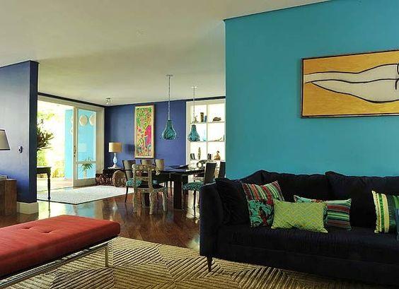 As salas de estar e jantar são integradas pelos tons de anil (S4055-R70B) e turquesa (S1555-B106), da Tintas Ypiranga. O banco estofado de seda é da Artefacto. Junto à porta de acesso ao jardim, quadro de Isabelle Tuchband. Sobre a mesa de acrílico âmbar, (Foto: Marcelo Magnani)
