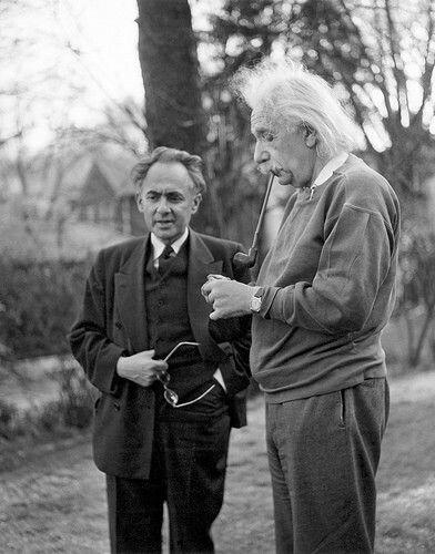 長いパイプをくわえて立っているアルベルト・アインシュタインの壁紙・画像