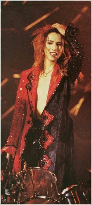 赤と黒のジャケットを着てドラムの前に立っているXJAPAN・YOSHIKIの画像