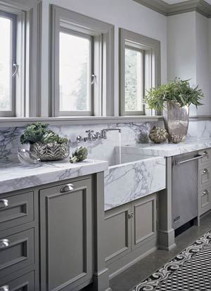 White marble paired with gray helps highlight the veining and when paired with a farmhouse sink, you get plenty of color. This kitchen also features the marble up the walls as a backsplash to make it even more elegant.
