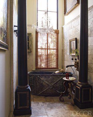 A zinc bathtub and a tumbled-travertine floor in the guest bath; a marble platter atop an Italian base serves as a table.