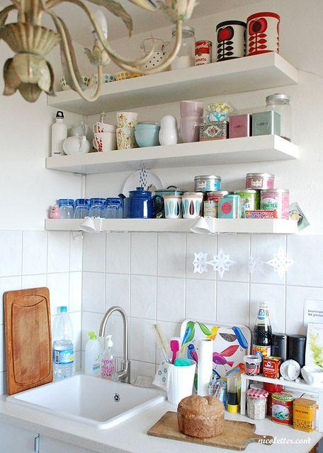 estantes flotantes blancos y expuestos en la cocina