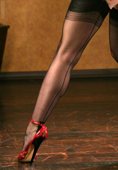 perfectly taut shapely leg encased in stockings and red high heels
