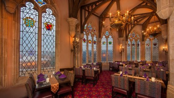 Chandeliers Over Several Tables Next To Leaded Windows With