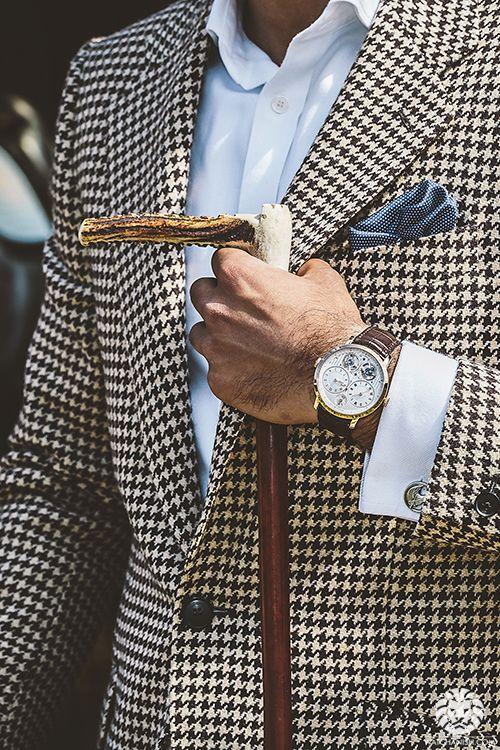 foto de un hombre con blazer con estampado pata de gallo, un bastón de madera, reloj y pañuelo. Excelente imagen personal