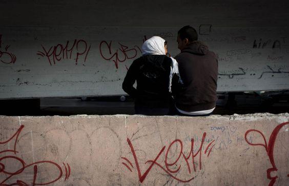 Il Cairo, Egitto  Una coppia egiziana seduta su un muro nei pressi di un ponte.