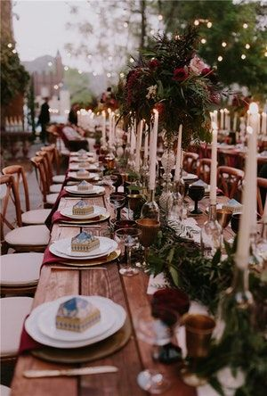 A Hogwarts-chic Harry Potter themed wedding was stunning while still on-theme. Deep red table elements, elevated candle sticks, and rustic wood furniture along with dark greenery and subtle strung lights evoked the feeling of everyone's favorite school if witchcraft.