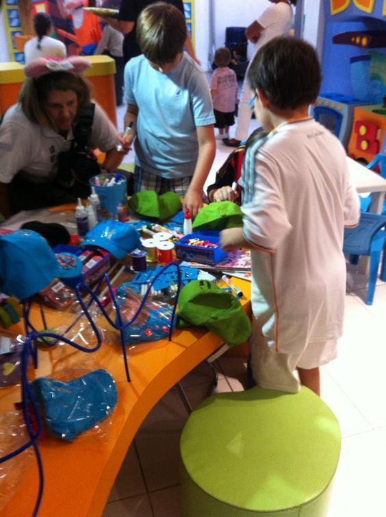 Crianças na oficina de customização de bonés.