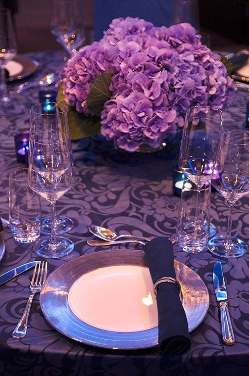 A dark purple table setting is accented with lighter purple hydrangea centerpieces.